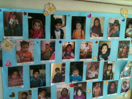 The children enjoy seeing their photos on this poster that hangs in the entrance hallway to Shalom.